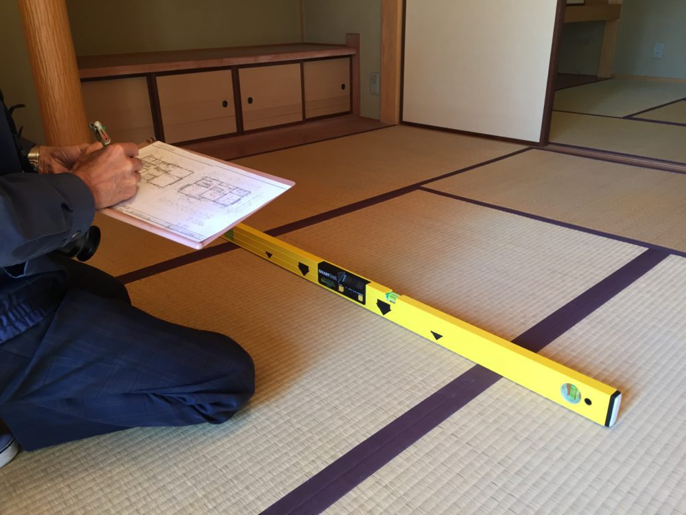 傾斜計を使って床・柱の傾斜を調べます。6/1000未満とするのが中古住宅の基準数値。