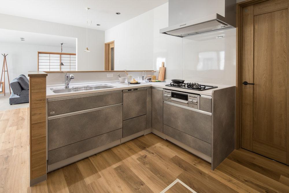 L型の対面キッチン。横にドアを設け、洗面脱衣室にアクセスできる動線に。