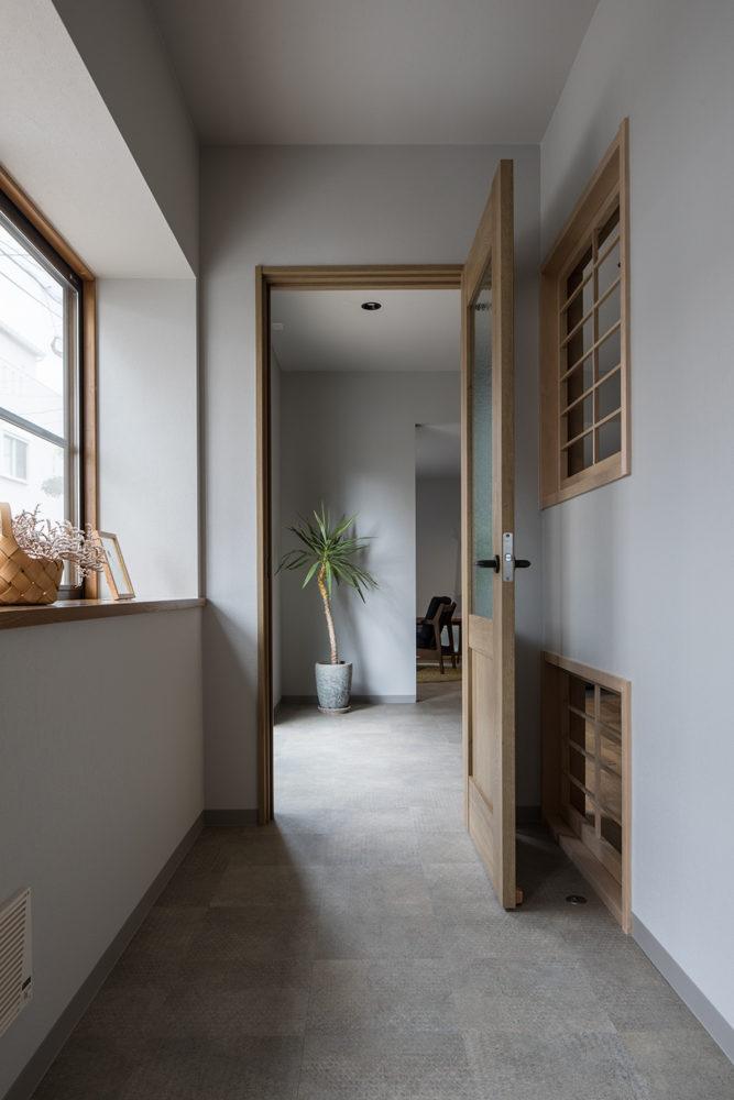 南に面した玄関ホール。キッチンに光が入るよう、間仕切り壁に格子をはめ込みました。